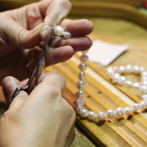 Woman hands threading a pearl necklace